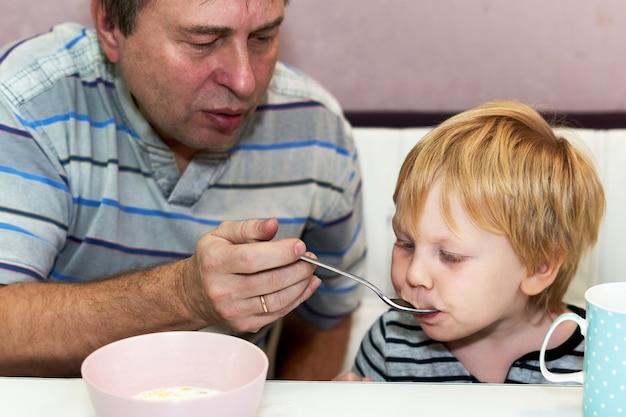 L'enfant Mange Avec La Cuillère Que Tient Le Grand-père Photo Premium