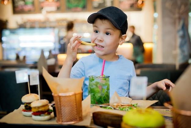 Un enfant mange fast food Photo Premium