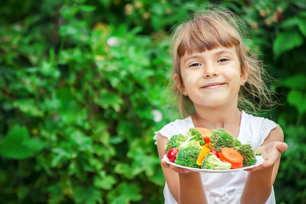 L'enfant mange des légumes. photo d'été. mise au point sélective. Photo Premium