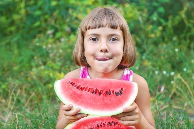 Enfant mange une pastèque dans le jardin Photo Premium