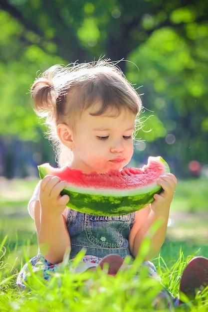 Un enfant mange de la pastèque. mise au point sélective. Photo Premium
