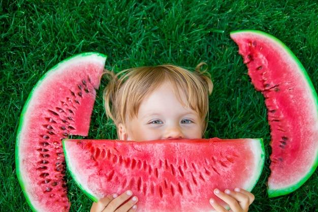 Enfant Mangeant La Pastèque Sur Le Parc En été Photo Premium