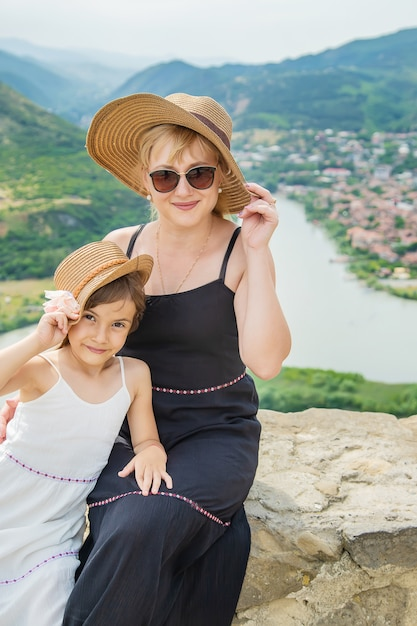 Un enfant avec une mère sur le fond des attractions de la géorgie Photo Premium