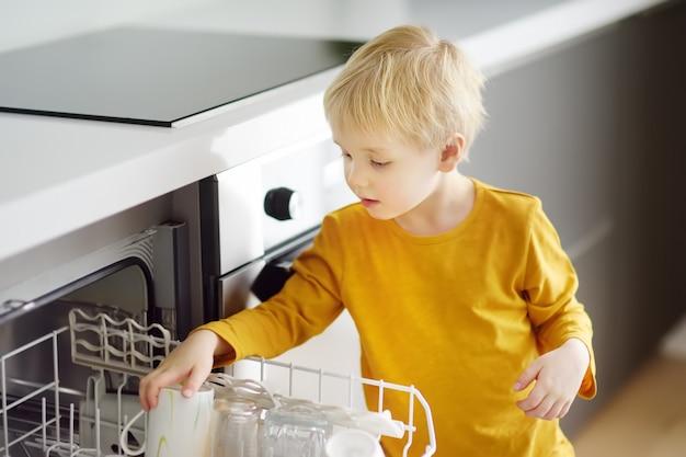 Enfant met la vaisselle sale dans le lave-vaisselle à la maison. fermer. Photo Premium