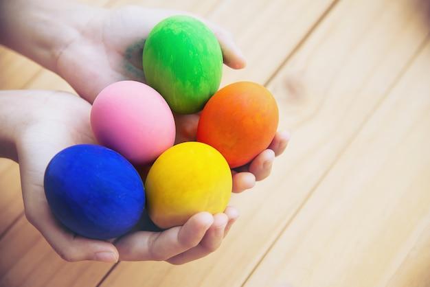 Enfant montrant des oeufs de pâques colorés avec bonheur - concept de célébration de vacances de pâques Photo gratuit