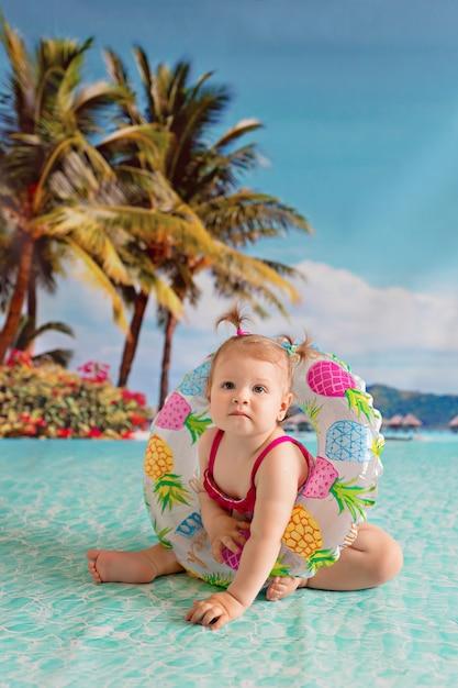 Enfant Nage Dans Une Bouée De Sauvetage D'une Pastèque Près D'une Plage De Sable Avec Des Palmiers Au Bord De La Mer Photo Premium