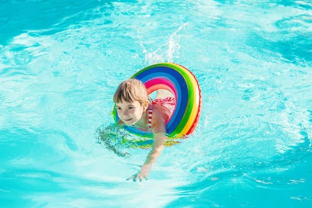 Un enfant nage dans une piscine avec un gilet de sauvetage. mise au point sélective. Photo Premium