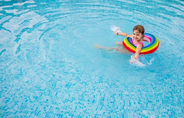 Un enfant nage dans une piscine avec un gilet de sauvetage. Photo Premium
