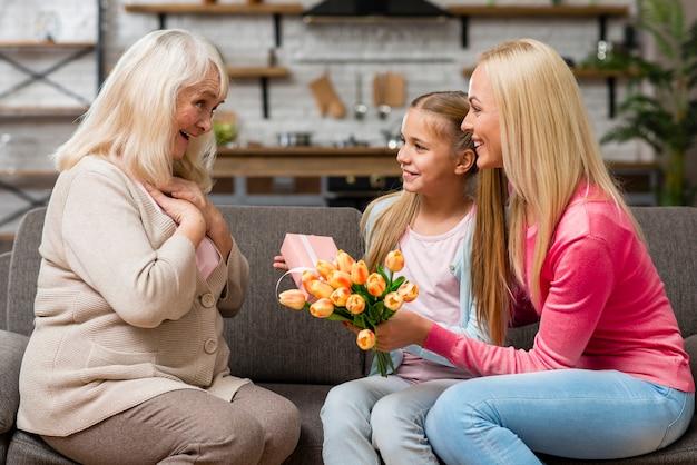 L'enfant Offre Un Bouquet De Fleurs à Sa Grand-mère Photo gratuit