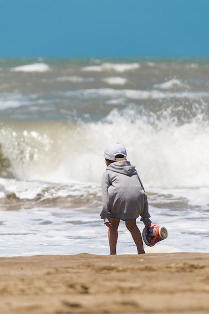 Enfant avec panier sur le bord de la mer près de l'eau Photo gratuit