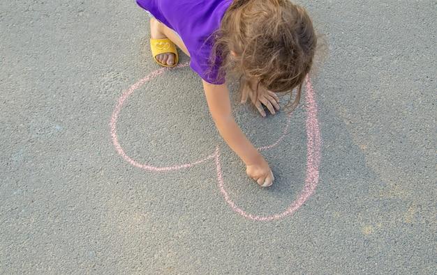 L'enfant peint la craie sur le coeur d'asphalte Photo Premium