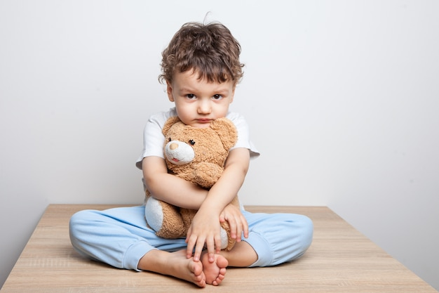 Enfant, Petit Garçon Assis Sur Une Table Embrasse Un Ours. Regardez Sérieusement La Caméra. Fatigue Et Découragement. Fond Blanc. Isolé Photo Premium