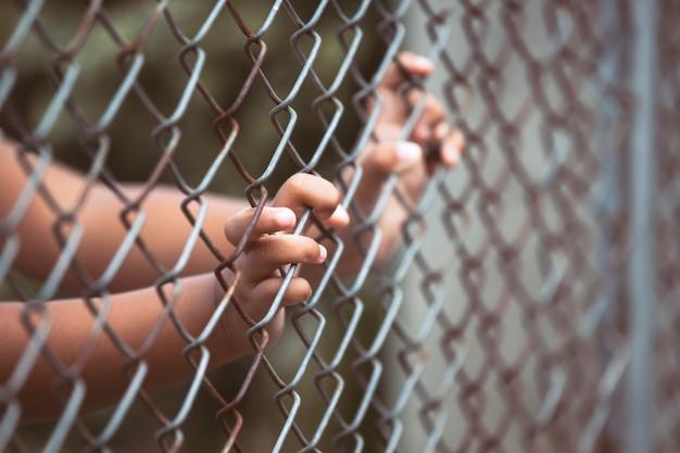 Enfant petite main de fille tenant maille d'acier dans la tonalité de couleur vintage Photo Premium