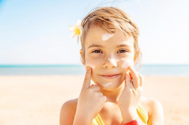 Enfant sur la plage frottis écran solaire. mise au point sélective. Photo Premium