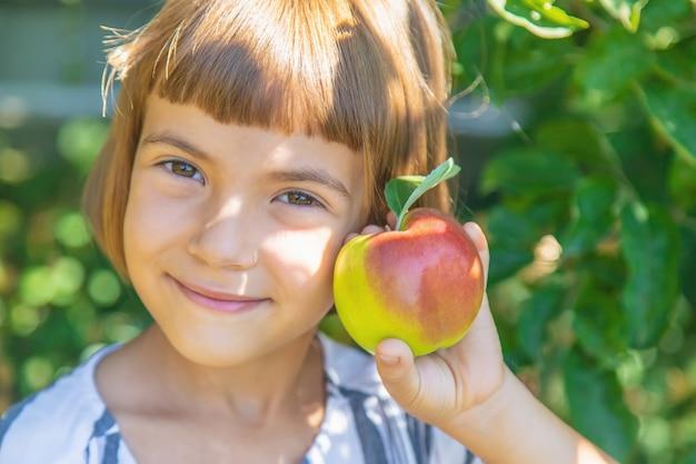 Enfant avec une pomme dans le jardin Photo Premium