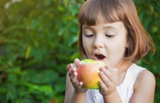 Enfant avec une pomme. mise au point sélective. la nature Photo Premium