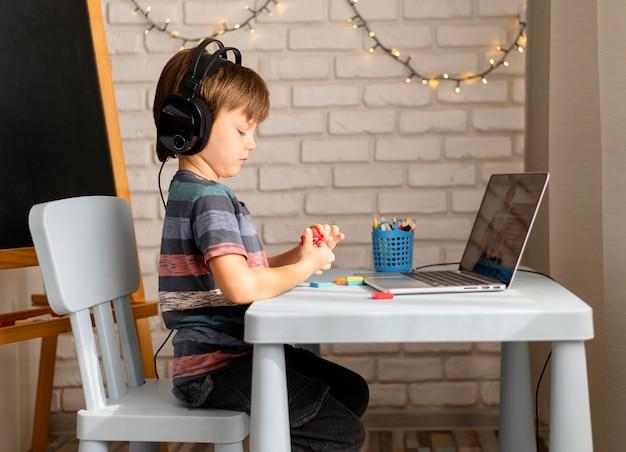 Enfant Portant Des écouteurs Assistant à Des Cours En Ligne Photo gratuit