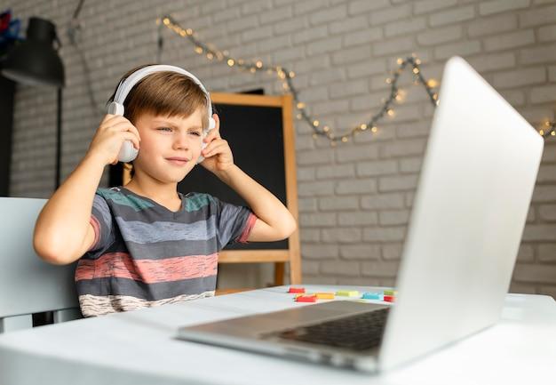 Enfant Portant Des écouteurs Assistant à Des Cours Virtuels Photo gratuit