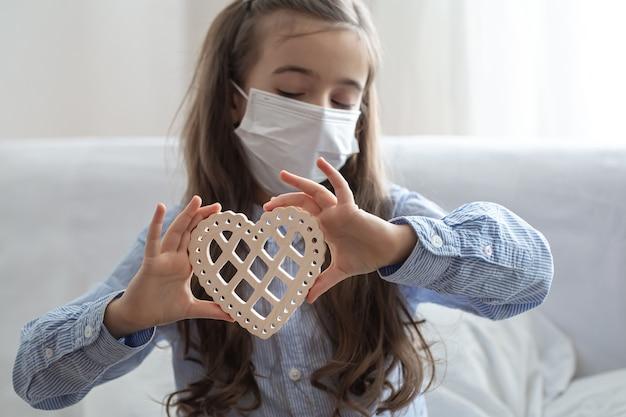 Enfant Portant Un Masque De Protection Médicale Pour La Protection De La Santé Contre Le Coronavirus, Tient Un Cœur En Bois. Photo gratuit