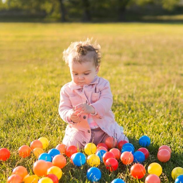 Enfant Portant Des Vêtements Roses Jouant Avec Des Boules En Plastique Photo gratuit