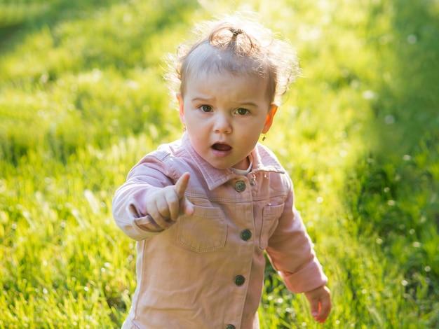 Enfant Portant Des Vêtements Roses Montrant Son Index Photo gratuit