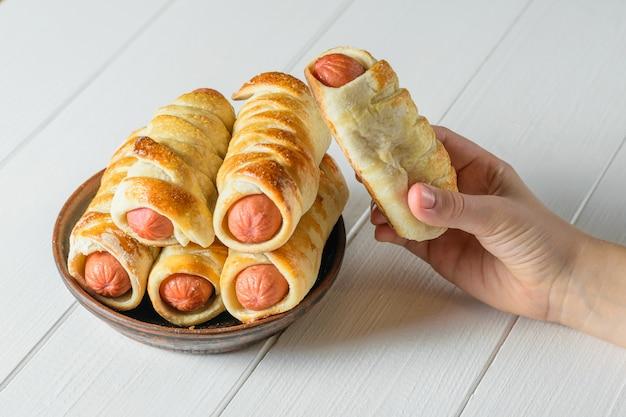 L'enfant prend une saucisse maison fraîchement cuite dans la pâte du bol en argile. Photo Premium