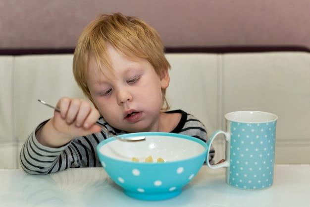 L'enfant Regarde La Fourchette Qu'il Mange Dans L'assiette Alors Qu'il était Assis à Table Photo Premium