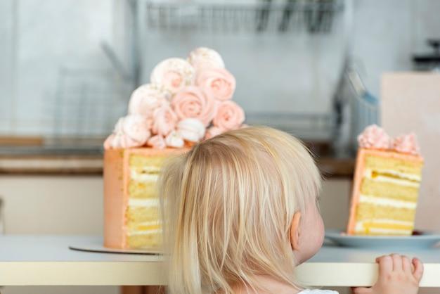 L'enfant Regarde Le Morceau De Gâteau. Gâteau De Créateur De Couleur Pêche. Photo Premium
