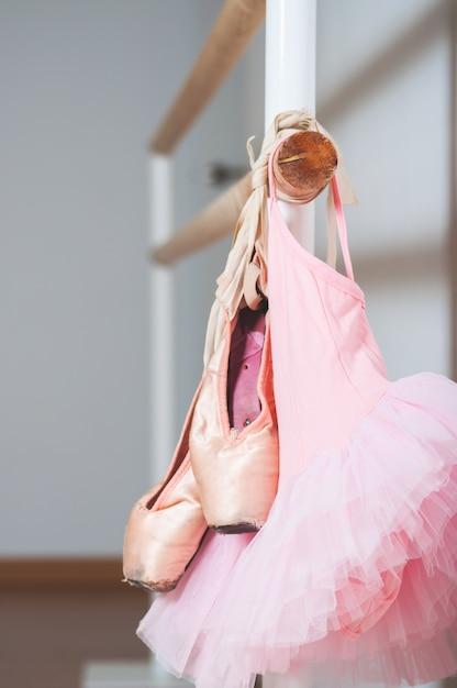 Enfant robe de ballet et chaussures de ballet tenant sur une barre de ballet. concept de danse. Photo Premium