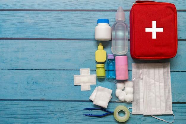 Enfant de sac de premiers soins vue de dessus avec des fournitures médicales sur fond de bois. Photo Premium