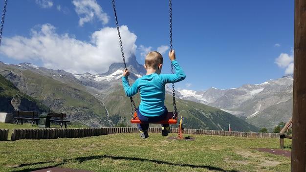 Enfant se balançant dans un parc avec vue sur le cervin Photo Premium