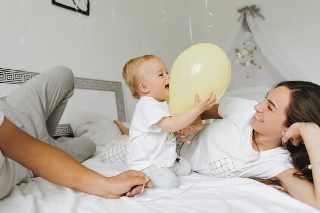 L'enfant se réjouit dans le ballon avec ses parents Photo gratuit
