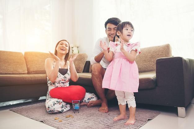 Enfant avec ses parents jouant au sol dans le salon Photo gratuit