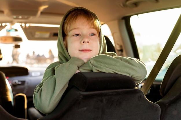Enfant Smiley à L'intérieur De La Voiture Lors D'un Voyage Sur La Route Photo gratuit