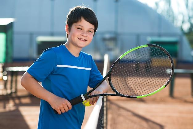 Enfant smiley reposant sur un filet de tennis Photo gratuit
