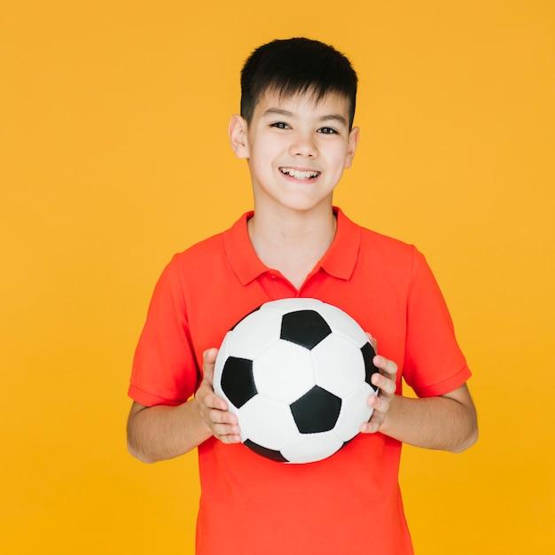 Enfant smiley vue de face tenant un ballon de football Photo gratuit