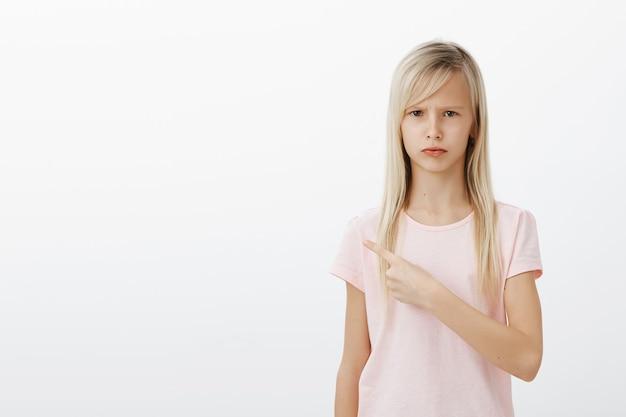 Enfant Sombre Déçu Pointant Vers La Gauche Photo gratuit