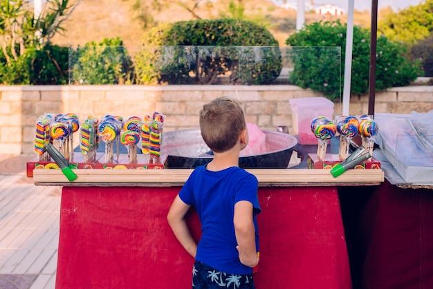 Enfant sur son dos en regardant une barre de chocolat à une foire Photo Premium