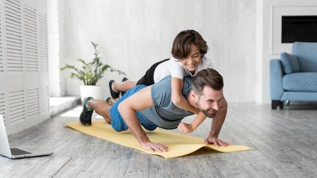 Enfant Et Son Père Faisant Du Sport à La Maison Photo gratuit