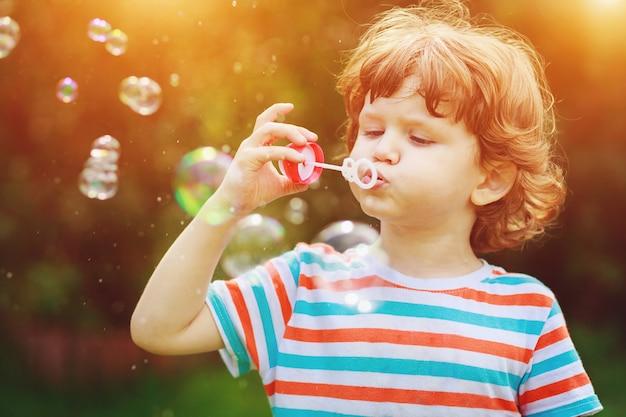Enfant soufflant des bulles de savon dans le parc de l'été. Photo Premium