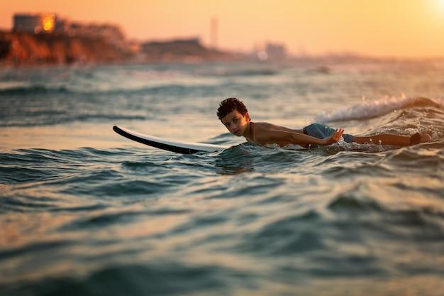 Enfant surfant sur une plage tropicale Photo Premium