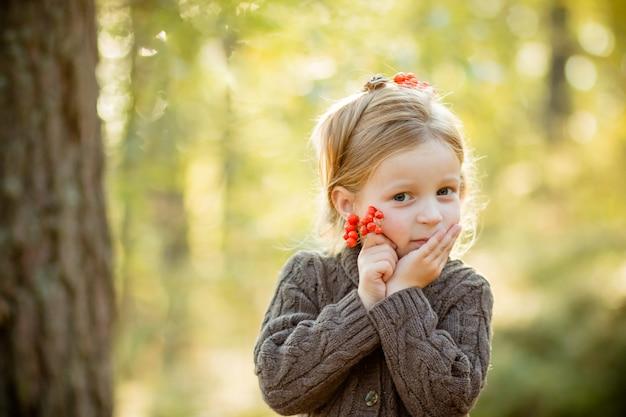 Enfant tenant des baies de rowan. Photo Premium