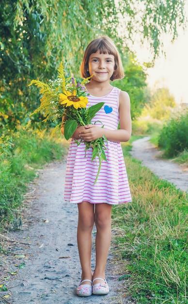 Enfant Tenant Un Bouquet De Fleurs Sauvages Dans Ses Mains | Photo Premium