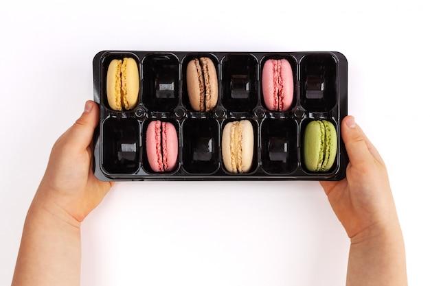 Enfant Tenant Le Paquet Avec Des Macarons Isolé Sur Blanc. Vue De Dessus Avec Espace Copie Photo Premium