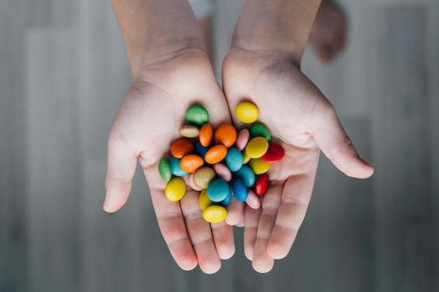 Un enfant tenant une poignée de bonbons Photo Premium