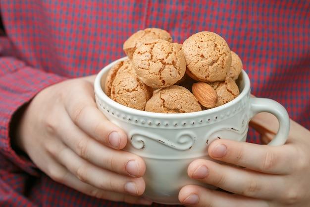 Enfant tient une tasse de biscuits aux amandes italiennes amaretti. biscuits croustillants. Photo Premium