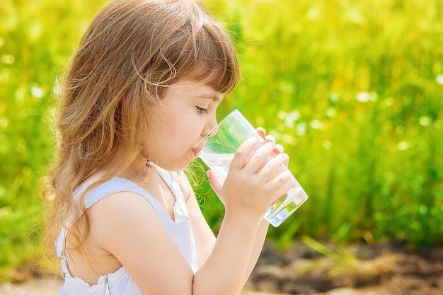 L'enfant tient un verre d'eau dans ses mains. mise au point sélective. Photo Premium