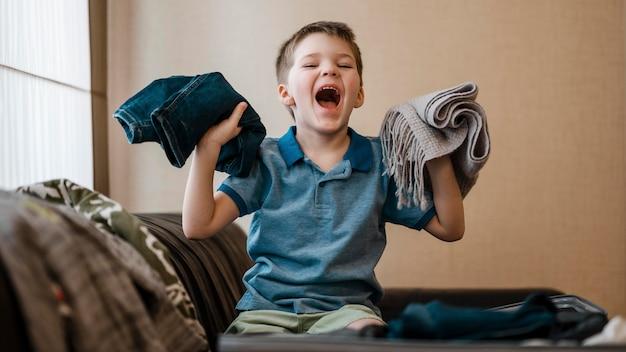Enfant De Tir Moyen Tenant Des Vêtements Photo gratuit