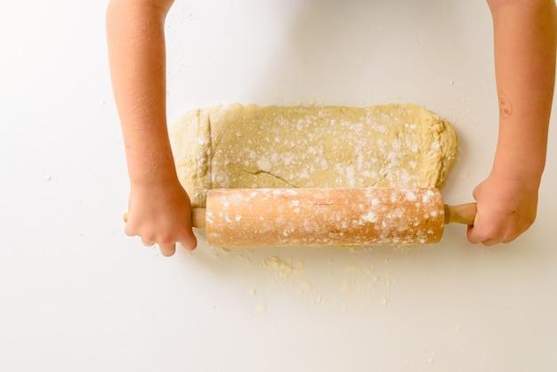 Enfant en train de pétrir la pâte d'une pizza, vue d'en haut. Photo Premium