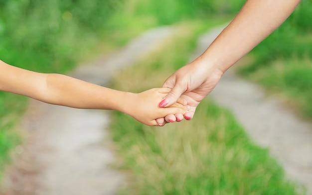L'enfant va main dans la main avec sa mère Photo Premium